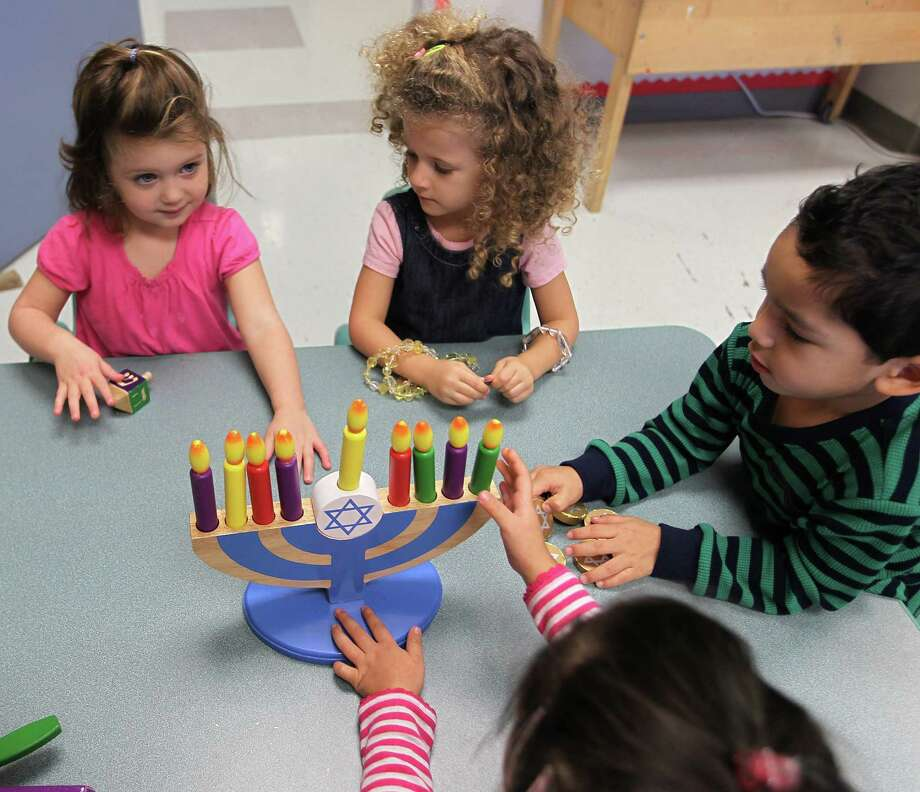 Naomi Block, left, plays with a toy menorah with Avery Fisher, center, and Kristofer Melendez, right, as Noam Noy, bottom, reaches in to play during the three-year-old pre-school class as they celebrate Hanukah, the Festival of Lights. Photo: Karen Warren, Houston Chronicle / © 2012  Houston Chronicle