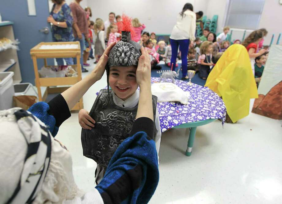 A pre-school student gets dressed as a Syrian Army soldier by Alana Shepetofsky, Judaic Curriculum Specialist, as they celebrate Hanukah, the Festival of Lights, at Bertha Alyce Early Childhood Center at the Evelyn Rubenstein Jewish Community Center of Houston. Photo: Karen Warren, Houston Chronicle / © 2012  Houston Chronicle