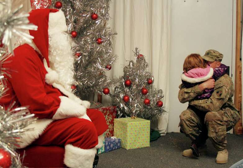Cpt. Stephen Olk hugs his five-year daughter, Brielle, after asking Santa for her father for Christm