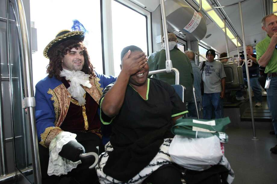 Captain Hook, aka Sam Byrd, of Theatre Under The Stars, sits next to Tamara Bohanna, of Houston, during a promotional ride for the up coming Peter Pan play on the METRORail , Friday, Dec. 7, 2012, in Houston.The play is being put on by Theatre Under The Stars and starts on December 11th at the Hobby Center. Photo: Nick De La Torre, Houston Chronicle / © 2012  Houston Chronicle