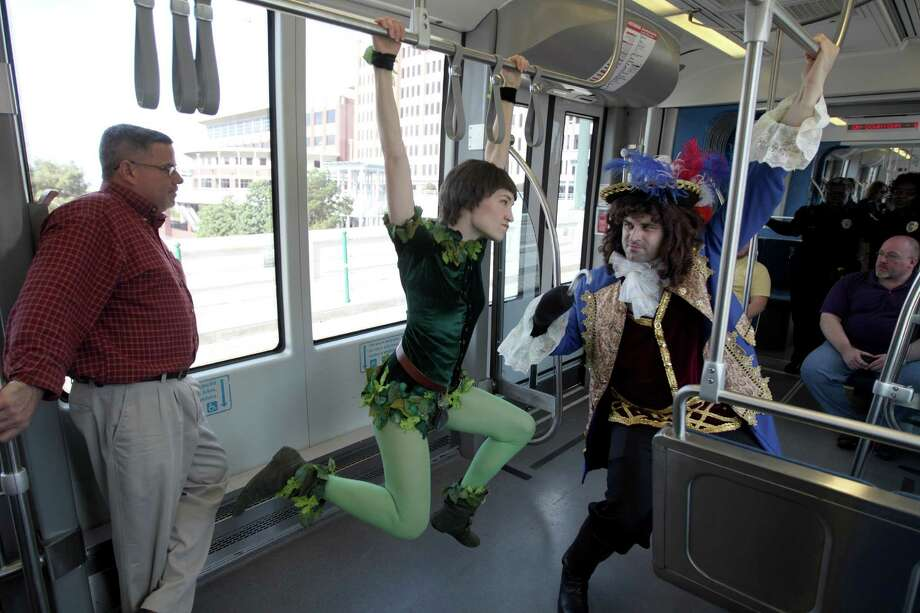Peter Pan, aka Kristin Warren, left, and Captain Hook, aka Sam Byrd, clown around during a promotional ride for the up coming Peter Pan play on the METRORail , Friday, Dec. 7, 2012, in Houston. Photo: Nick De La Torre, Houston Chronicle / © 2012  Houston Chronicle