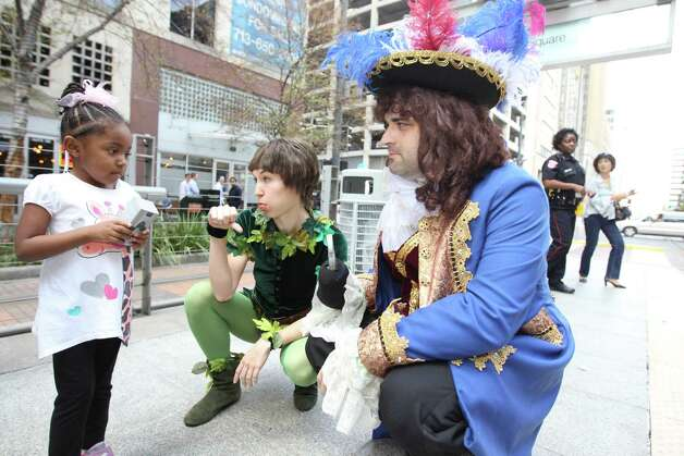 Mia Stanford, 4, of Houston, left, visits with Peter Pan and Capt. Hook during a promotional outing for the up coming Peter Pan play on a METRORail platform at Macy's. Photo: Nick De La Torre, Houston Chronicle / © 2012  Houston Chronicle