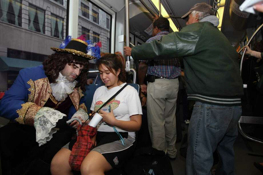 Captain Hook, looks through Carina Torres' purse as he and Peter Pan do a promotional ride for the up coming Peter Pan play on the METRORail. Photo: Nick De La Torre, Houston Chronicle / © 2012  Houston Chronicle