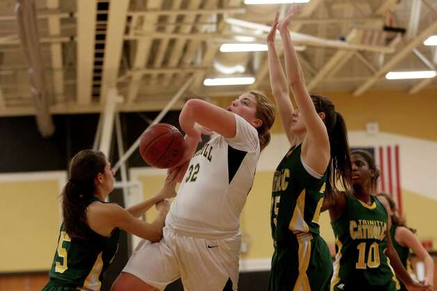 Mike Ross Connecticut Post freelance -Trumbull High School's #32 Erin Moore gets fouled while driving to the basket from Trinity Catholic's #5 Kellie Hurd during first action on Friday evening. On right defending is Trinity Catholic's # 25 Allison Palma. Photo: Mike Ross / Connecticut Post Freelance