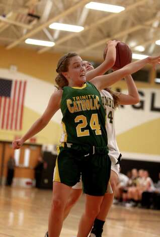 Mike Ross Connecticut Post freelance -Trumbull High School's #14 Danielle McGillicuddy drives to the basket and scores on Trinity Catholic's #24 Siobhan Kirby during first half action on Friday evening. Photo: Mike Ross / Connecticut Post Freelance