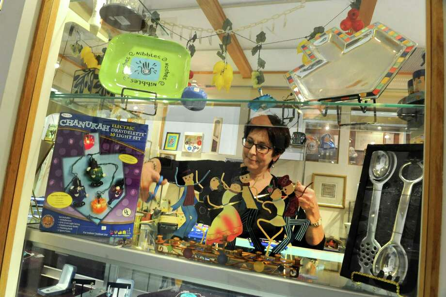 Store manager Eve Cameron wraps a Hanukkah gift at the Hadar Gift and Book Shop at Temple Israel on Friday Dec. 7, 2012 in Albany, N.Y.  (Lori Van Buren / Times Union) Photo: Lori Van Buren