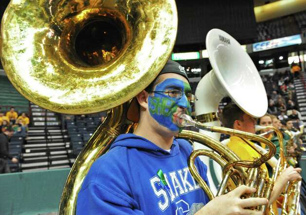 Siena College Pep Band member and Shaker High grad,  Matthew Lorini wears a Shaker sweatshirt and a blue and green ribbon in honor of the Shaker and Shen students who died last Saturday, as he plays his Sousaphone during Friday's game with Rider University at the Times Union Center in Albany  Dec. 7, 2012. All the members of Siena's Pep Band wore blue and green ribbons.   (John Carl D'Annibale / Times Union) Photo: John Carl D'Annibale / 00020393A