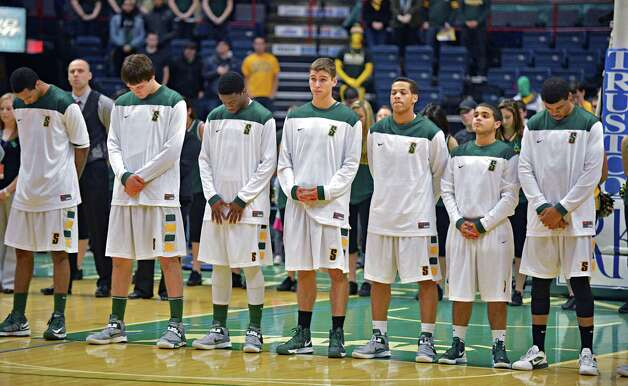 Siena College players during a moment of silence in remembrance of the Shen students who died last Saturday during Friday's game with Rider University at the Times Union Center in Albany  Dec. 7, 2012. Photo: John Carl D'Annibale / 00020393A