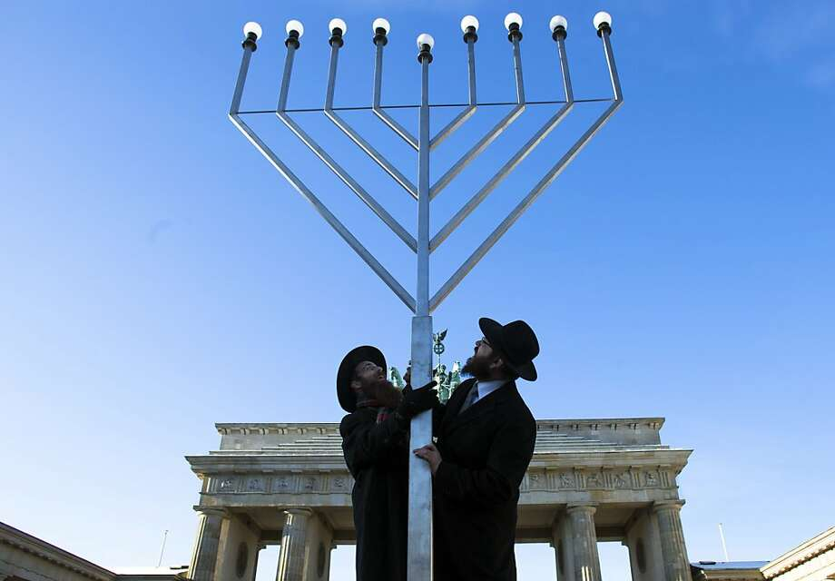 Rabbi Yehuda Teichtal, right, and Rabbi Segal Shmoel, left, install a giant Hanukkah Menorah, at the Pariser Platz in front of the Brandeburg Gate in Berlin, Friday, Dec. 7, 2012. The eight day Jewish Festival of Lights, Hanukkah will start on Dec. 8. Photo: Markus Schreiber, Associated Press