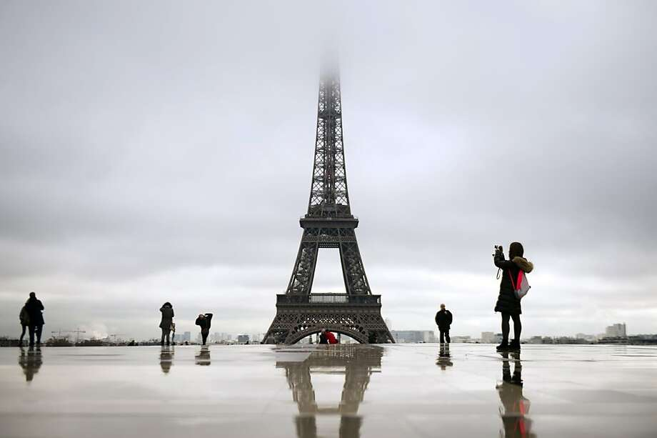 People walk on the Trocadero square as the top of the Eiffel tower is taken in the mist on December 7, 2012 in Paris. Photo: Lionel Bonaventure, AFP/Getty Images