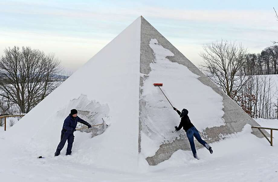 Workers clean a model replica of Cheops Pyramid of Giza, after snowfall in landscape park Miniwelt (Miniworld), in Lichtenstein, eastern Germany, Friday, Dec. 7, 2012.  The cultural park Miniworld presents about 100 original and true-to detail buildings and technical facilities at a 1:25 scale. Photo: Jens Meyer, Associated Press