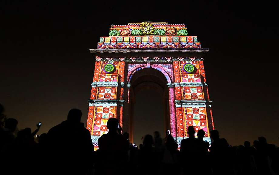 People watch as a laser show illuminates India Gate war memorial in New Delhi, India, Friday, Dec. 7, 2012. The event marked the culmination of the various Japanese cultural events held in India to commemorate the sixtieth anniversary of Japan India diplomatic relations. Photo: Altaf Qadri, Associated Press