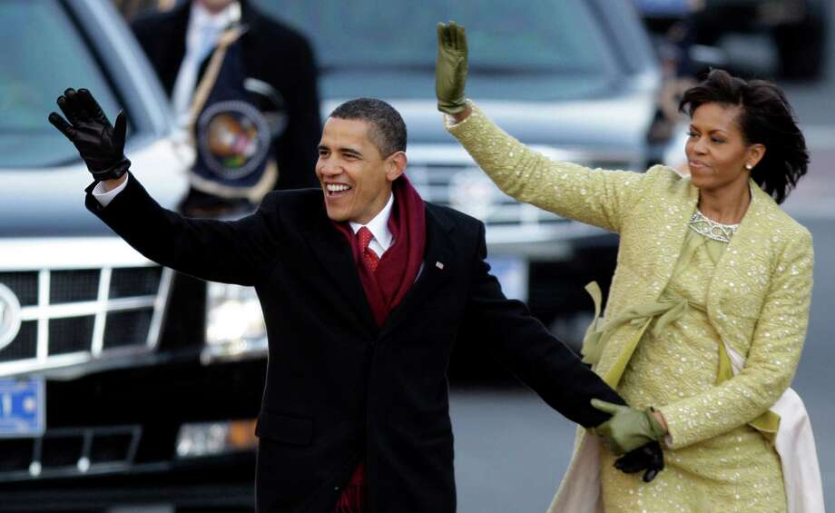 FILE - This Jan. 20, 2009 file photo shows President Barack Obama and first lady Michelle Obama waving as they walk down Pennsylvania Avenue on their way to the White House in Washington, after taking the presidential oath. In a reversal from four years ago, President Barack Obama will accept unlimited sums of money from corporations and individuals to pay for events surrounding his Inauguration, a spokeswoman said Friday.  (AP Photo/Alex Brandon, File) Photo: Alex Brandon