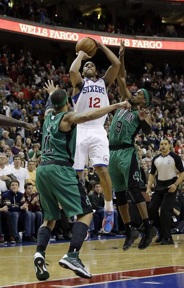 Philadelphia's Evan Turner connects for the go-ahead basket between Boston's Courtney Lee (left) and Rajon Rondo. Photo: Matt Slocum, Associated Press