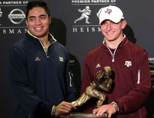 Notre Dame linebacker Manti Te'o, left, and Texas A&M quarterback Johnny Manziel, two of the three Heisman Trophy finalists, pose with the Heisman Trophy during a media availability, Friday, Dec. 7, 2012 in New York.  (AP Photo/Mary Altaffer) Photo: Mary Altaffer