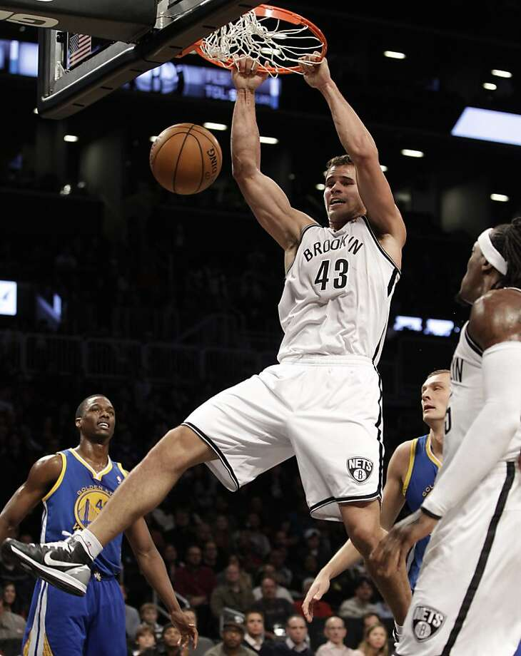 Golden State Warriors forward Harrison Barnes (40) watches as Brooklyn Nets forward Kris Humphries (43) dunks in the first half of an NBA basketball game at Barclays Center, Friday, Dec. 7, 2012, in New York. (AP Photo/Kathy Willens) Photo: Kathy Willens, Associated Press