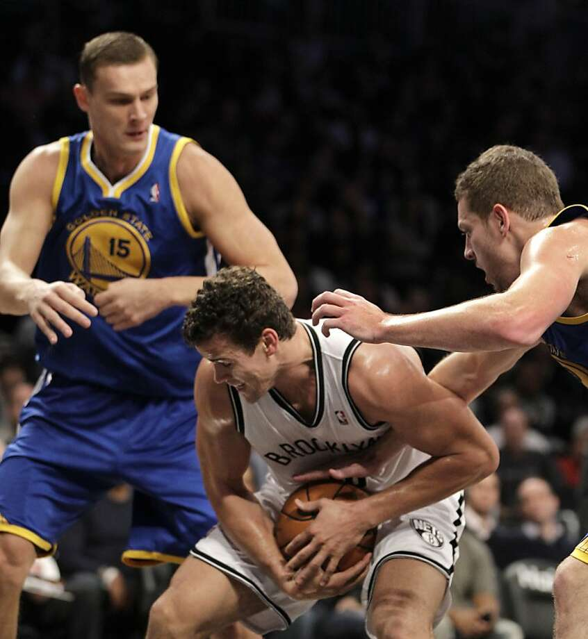 Brooklyn Nets forward Kris Humphries (43) protects the ball from Golden State Warriors forward David Lee (10) as Warriors forward Andris Biedrins (15) watches after Humphries snagged a rebound in the first half of an NBA basketball game at Barclays Center, Friday, Dec. 7, 2012 in New York. (AP Photo/Kathy Willens) Photo: Kathy Willens, Associated Press