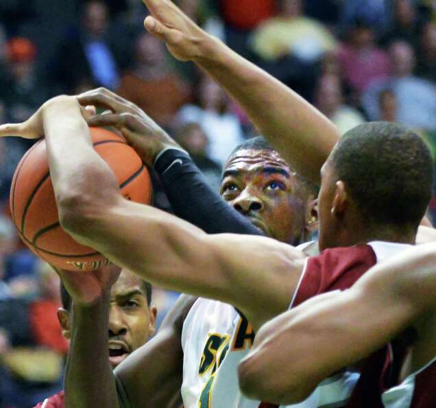 Siena's #1 O.D.Anosike, center, is fouled on his way to the basket during the Metro Atlantic Athleti