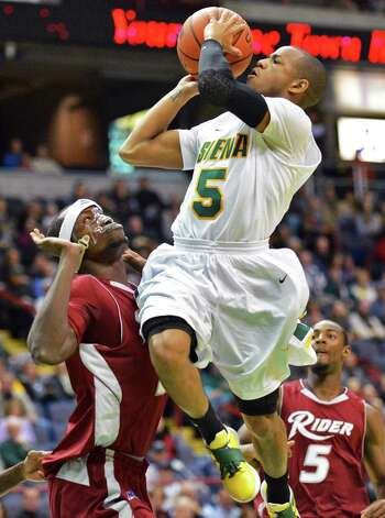 Siena's #5 Evan Hymes goes to the basket as Rider's #21 Dera Nd-Ezuma defends during the Metro Atlantic Athletic Conference opener at the Times Union Center in Albany Friday Dec. 7, 2012.  (John Carl D'Annibale / Times Union) Photo: John Carl D'Annibale / 00020381A