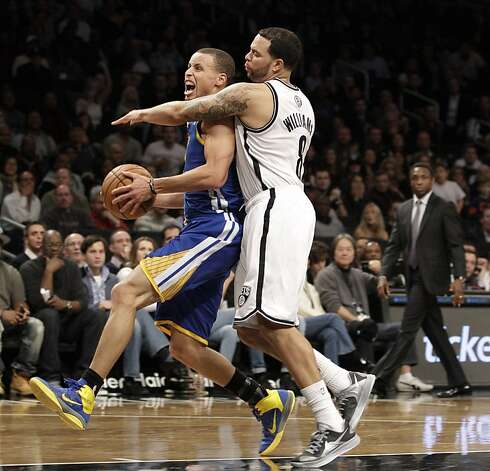 Brooklyn Nets guard Deron Williams (8) defends as Golden State Warriors guard Stephen Curry (30) goes to the basket during the second half of the Warriors 109-102 win in an NBA basketball game at the Barclays Center, Friday, Dec. 7, 2012, in New York. (AP Photo/Kathy Willens) Photo: Kathy Willens, Associated Press