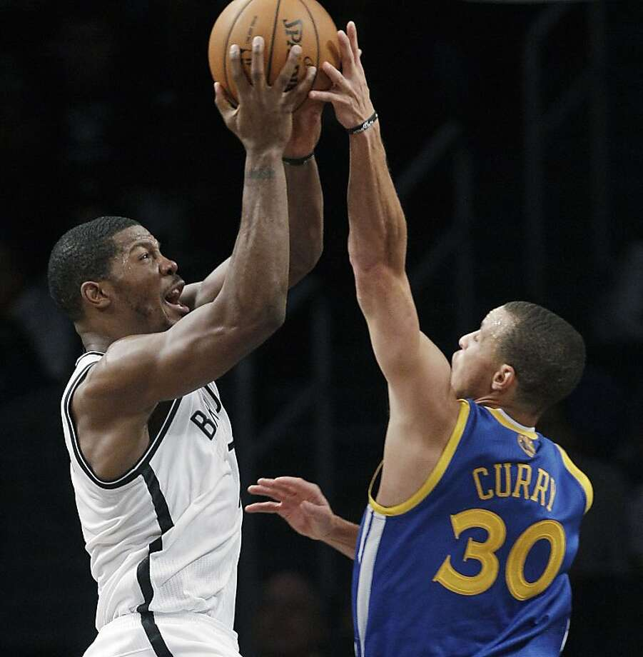 Golden State Warriors guard Stephen Curry (30) blocks a shot by Brooklyn Nets guard Joe Johnson (7) during the second half of an NBA basketball game, Friday, Dec. 7, 2012, in New York. The Warriors won 109-102.(AP Photo/Kathy Willens) Photo: Kathy Willens, Associated Press