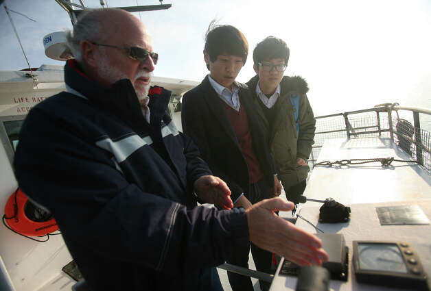 From left; Catherine Moore boat Capt. Paul Lepanto talks with visiting Korean high school students Park Jaesung and Jeong Haerang during a boat trip to the Aquaculture School's seaweed farm of Fairfield on Tuesday, December 4, 2012. Photo: Brian A. Pounds / Connecticut Post