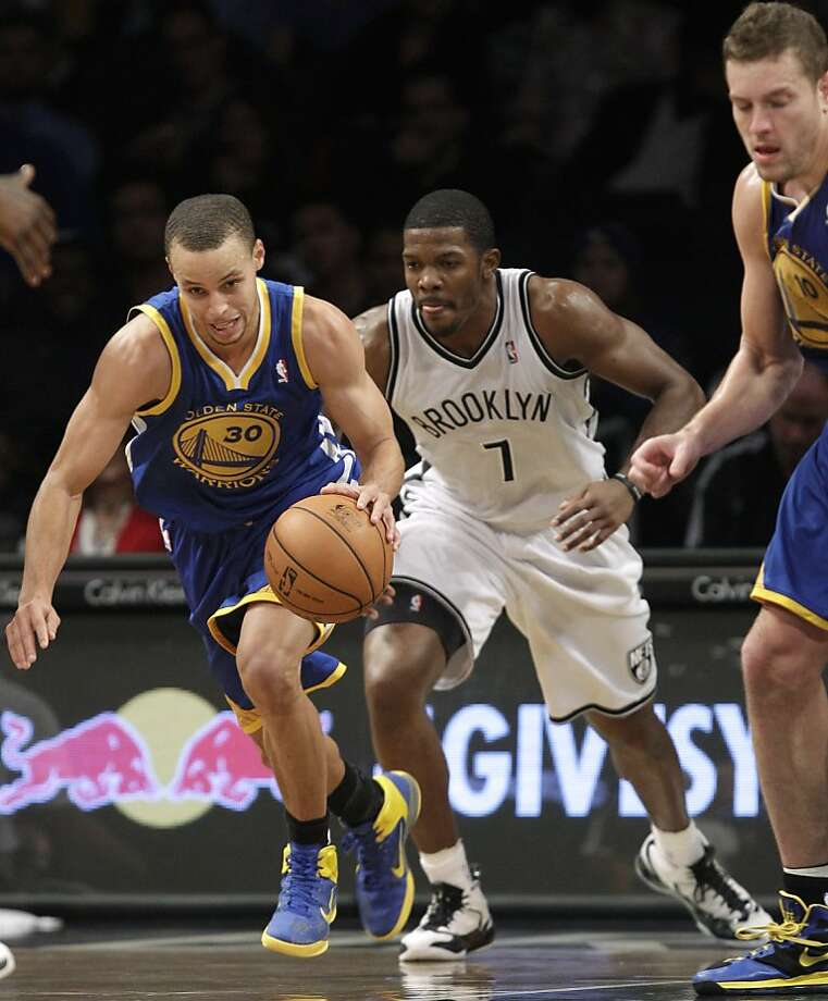 Golden State Warriors guard Stephen Curry (30) brings the ball up next to Brooklyn Nets guard Joe Johnson (7) during the second half of an NBA basketball game, Friday, Dec. 7, 2012, in New York. The Warriors defeated the Nets 109-102. (AP Photo/Kathy Willens) Photo: Kathy Willens, Associated Press