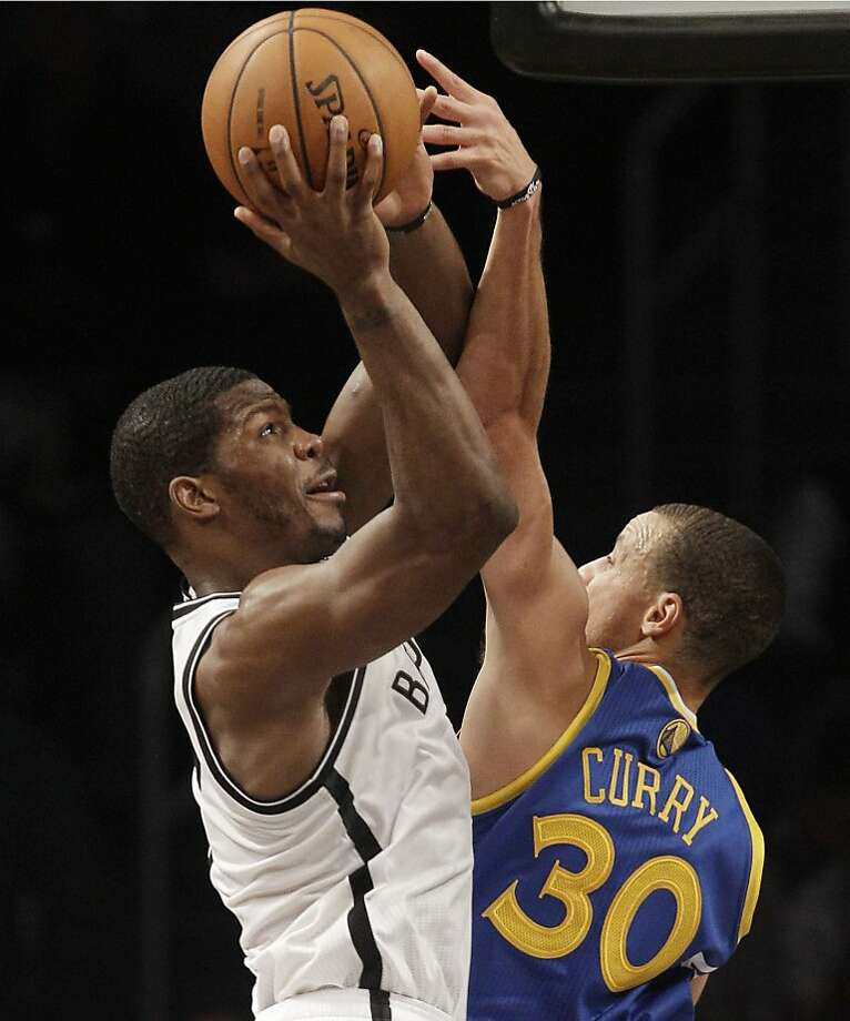 Golden State Warriors guard Stephen Curry (30) blocks a shot by Brooklyn Nets guard Joe Johnson (7) in the second half of their NBA basketball game at the Barclays Center, Friday, Dec. 7, 2012, in New York. (AP Photo/Kathy Willens) Photo: Kathy Willens, Associated Press