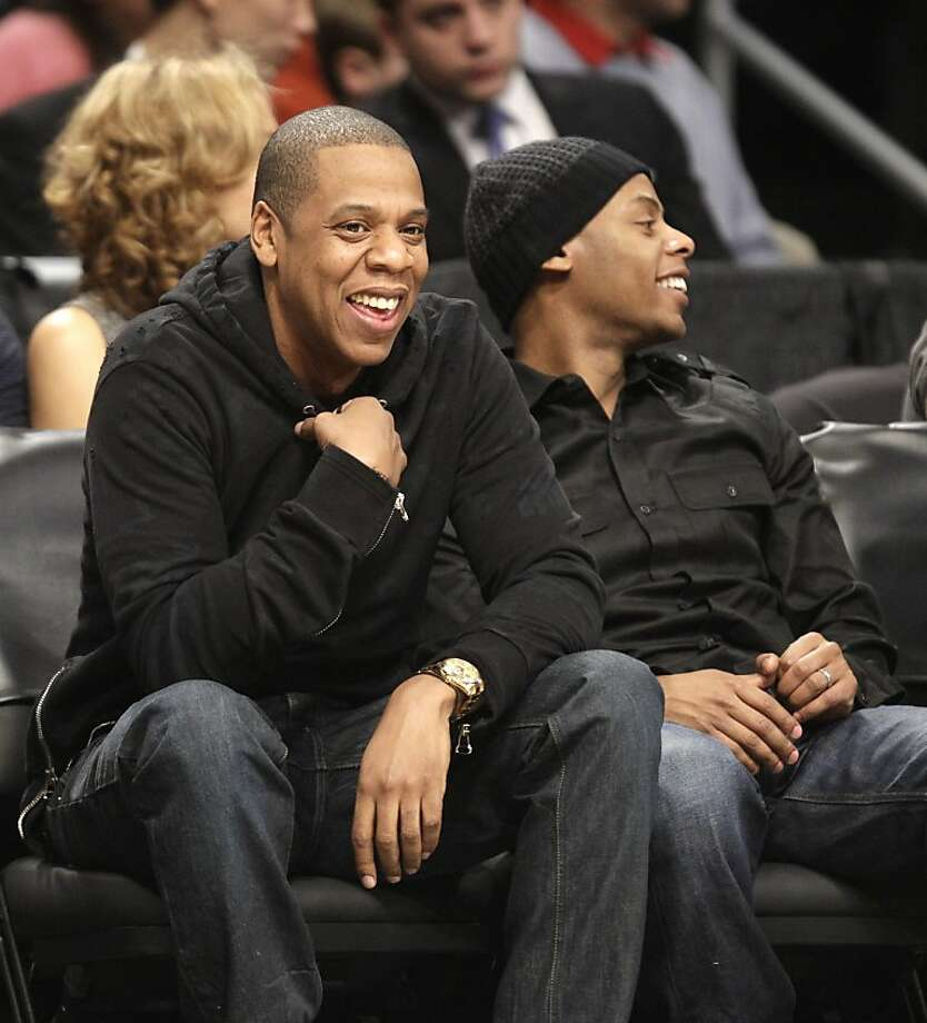 Jay-Z, left, a part-owner of the Brooklyn Nets, smiles as he watches the Nets play the Golden State Warriors in an NBA basketball game, Friday, Dec. 7, 2012, in New York. The Warriors won 109-102. (AP Photo/Kathy Willens) Photo: Kathy Willens, Associated Press