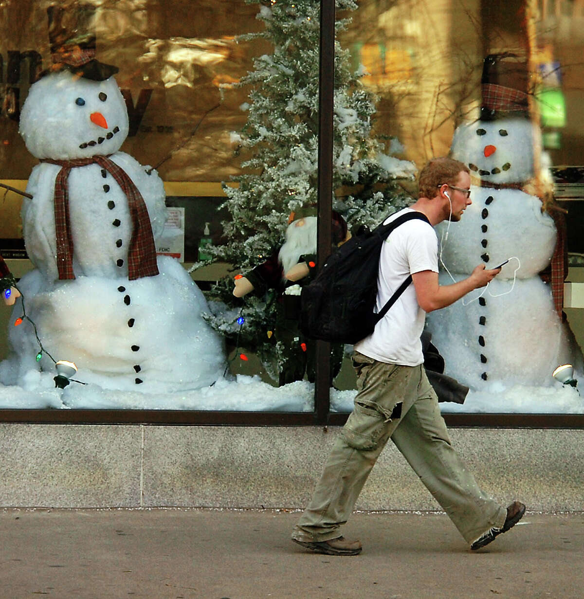 A man walks past a holiday window display during unseasonably warm weather at the Penn Security Bank & Trust building on Spruce Street in downtown Scranton, Pa., on Tuesday, Dec. 4, 2012. (AP Photo/The Scranton Times-Tribune, Butch Comegys)