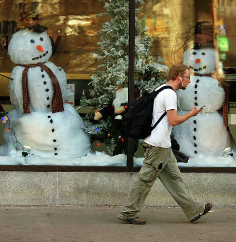 A man walks past a holiday window display during unseasonably warm weather at the Penn Security Bank & Trust building on Spruce Street in downtown Scranton, Pa., on Tuesday, Dec. 4, 2012. (AP Photo/The Scranton Times-Tribune, Butch Comegys) Photo: Butch Comegys, MBO / The Scranton Times & Tribune