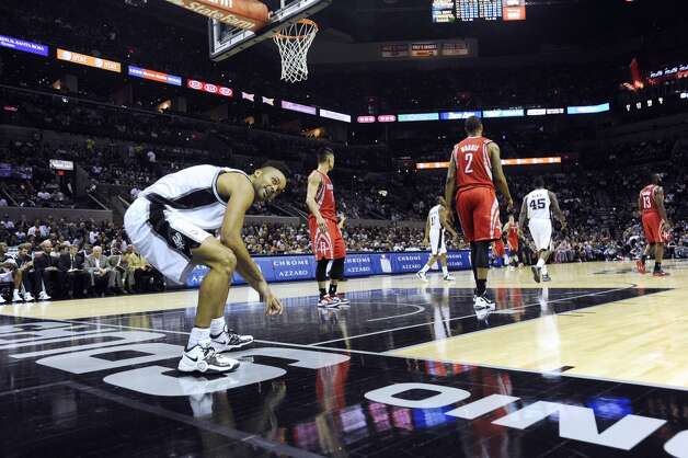 Tony Parker of the San Antonio Spurs reacts after being knocked down during a layup attempt against the Houston Rockets during NBA action at the AT&T Center on Friday, Dec. 7, 2012. Parker was hoping for a foul call against his defender. (Billy Calzada / San Antonio Express-News)