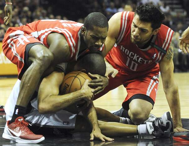 Toney Douglas, left, and Carlos Delfino of the Houston Rockets tie up Tony Parker of the San Antonio Spurs, causing a jump ball call, during NBA action at the AT&T Center on Friday, Dec. 7, 2012. (Billy Calzada / San Antonio Express-News)