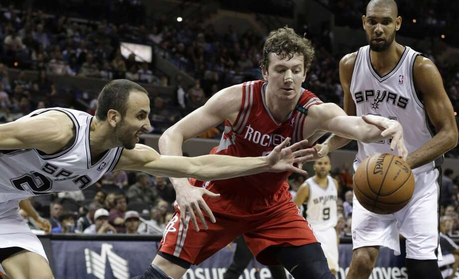 Rockets center Omer Asik tries to maintain possession against the Spurs' defense. (Eric Gay / Associated Press)