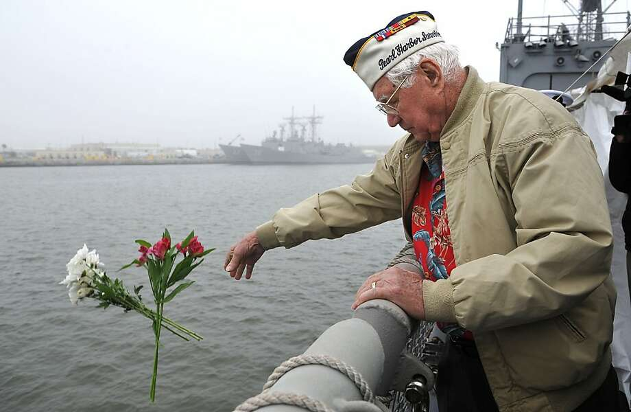 Pearl Harbor survivor Duane H. Reyelts  drops flowers into the Mayport ship basin in honor of those who perished at Pearl Harbor during a ceremony remembering the 71st anniversary of the attack on Pearl Harbor on aboard the USS De Wert on Friday, Dec. 7, 2012, at the Naval Station Mayport in Jacksonville, Fla.  (AP Photo/Florida Times-Union, Bruce Lipsky) Photo: Bruce Lipsky, Associated Press