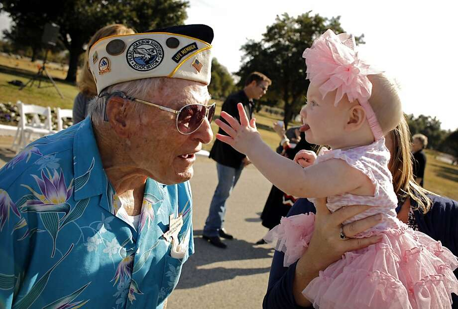 Pearl Harbor survivor Kenneth Adams, left, leans out as 6-month-old Kalani Parsons, the great-granddaughter of fellow survivor Charles Peters, reaches to touch his medals during the Pearl Harbor 71st Anniversary Memorial Service Friday, Dec. 7, 2012 at Laurel Land Memorial Park in Dallas. (AP Photo/The Dallas Morning News, G.J. McCarthy)  MANDATORY CREDIT; MAGS OUT; TV OUT; INTERNET OUT; AP MEMBERS ONLY Photo: G.J. McCarthy, Associated Press