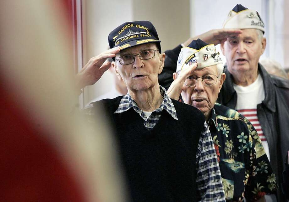 Jesse Dunnagan of Prairie Village, left, Edmund Russell of Lenexa, second from left, Jack Carson of Overland Park, right, all survivors of the Japanese attack on Pearl Harbor in World War II salute during the Pledge of Allegiance at a Pearl Harbor memorial ceremony, Friday, Dec. 7, 2012 in Mission, Kan. (AP Photo/The Kansas City Star, Fred Blocher) Photo: Fred Blocher, Associated Press