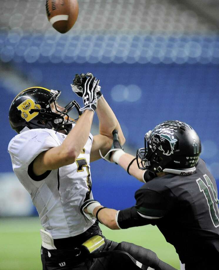 Brennan's Dillon Gatian (7) leaps for the ball ahead of Cedar Park's Lane Waller during a 4A high school football playoff game, Friday, Dec. 7, 2012, at the Alamodome in San Antonio. Cedar Park won 32-7. Photo: Darren Abate, For The Express-News