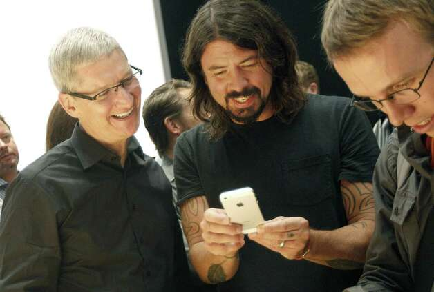 FILE -In this Wednesday, Sept. 12, 2012, file photo, Apple CEO Tim Cook, left, talks with musician Dave Grohl of the Foo Fighters as they look at an iPhone 5 during an Apple event in San Francisco.  Apple is emerging as a gentler, cuddlier corporate citizen in the year after the death of CEO and co-founder Steve Jobs. CEO Tim Cook's announcement that the company is moving a Mac production line to the U.S. is just the latest step in a charm offensive designed to soften Apple's image.  (AP Photo/Jeff Chiu) Photo: Jeff Chiu