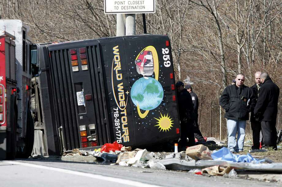 FILE--In this photo from Saturday, March 12, 2011, emergency personnel investigate the scene of a bus crash on Interstate-95 in the Bronx borough of New York. A verdict has been reached in a manslaughter case against the bus driver Ophadell Williams, charged in the crash that killed 15 passengers.  Williams has pleaded not guilty. He says a tractor-trailer cut him off and he lost control. The bus carrying gamblers coming from a Connecticut casino was sheared open like a sardine can when it struck a pole.  (AP Photo/David Karp, File) Photo: David Karp