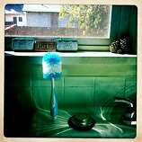 "This is a brush for Quinn's bottle on our sink with a note behind it made of gum and mints Craig picked up for me on his travels, ""Jamie I love you Craig,"" it reads. On the top right of the frame are three pine cones I picked up on one of my walks with Quinn that represent our family. The taller, grey one on the right is Craig. I'm the reddish-colored one, leaning on Craig. And Quinn is the little one in the middle."