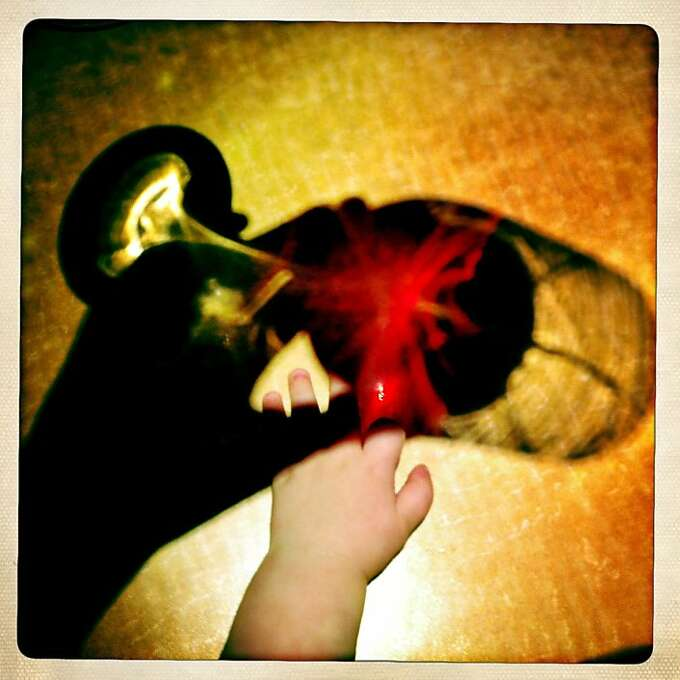 """When a friend asked where I wanted to go to happy hour, I said, """"wherever people won't judge me for drinking with a baby."""" We ended up at a restaurant, where Quinn was fascinated by the reflection of my wine-filled glass on the table. Photo: Jamie Cotten"""
