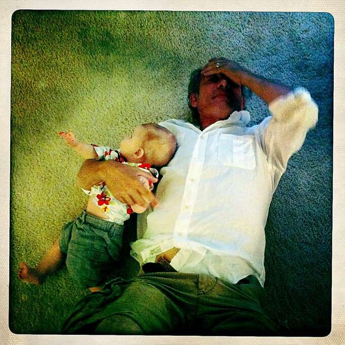 Craig lies on the floor, exhausted, with Quinn during a barbecue at a friend's house as Quinn tries to crawl away. Photo: Jamie Cotten