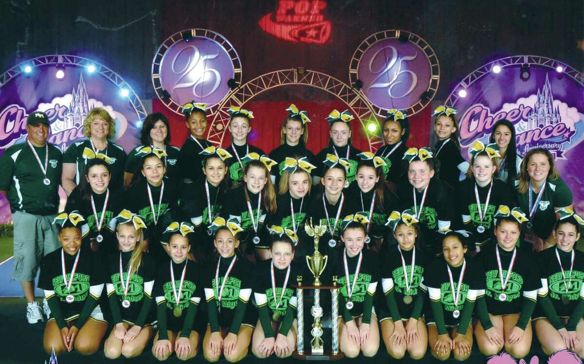 """The New Milford Bulls' Pop Warner Junior Midget cheerleaders created magic Dec. 5, 2012 at the Walt Disney World resort in Orlando, Fl.. The 25 New Milford athletes won their category and earned top honors highest score in their session to claim a championship at the national youth cheerleading competition. The title capped a run of success for the New Milford girls, who previously had won state and New England regional laurels to qualify for the national event. """"It has been a long time coming for this hard- working team,"""" said Bulls' cheerleading commissioner Mindi Sarko, who noted the girls' season-long motto, """"One Team, One Dream,"""" had now come true. Shown here in a posed photo during the competition are, from left to right, front row, Samara Jenkins, Codi Sealund, Tianna Wells, Olivia Thalassinos, Lauren Lombardo, Megan Lynch, Mia Fyler, Trish Lilley, Micayla Flynn and Hannah Seigel; middle row, Leah Cognato, Joanna DeLima, Alisson Haywood, Michaela Ferlow, Shania Ek, Emily McGuire, Taylor Franzese, Emily Spagnolo, Danielle Kwapien and coach trainee Meghan Cognato; and, back row: assistant coach Tom Cognato, head coach Sherri Cognato, Bulls' cheer commissioner Mindi Sarko, Ivey Collins, Gabriella Main, Brittany Karaz, Megan Radcliff, Briana Podyma, Ivana Perez and demonstrator Lexi Franzese. Not shown are assistant coach Jessica Seigel and demonstrator Meghan Timan. For the story and more photos, see Page S? Courtesy of the New Milford Bulls"""