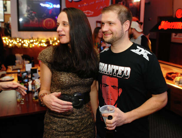Tara and Mike Schneider, of North Haven, attend the party to watch Nick Newell fight for the MMA Lightweight Championship in Nashville, Tenn. which was televised live at Orange Ale House in Orange, Conn. on Friday December 7, 2012. The Schneider's, who befriended the Newell family just recently, have a son with a similar handicap as Nick. Photo: Christian Abraham / Connecticut Post
