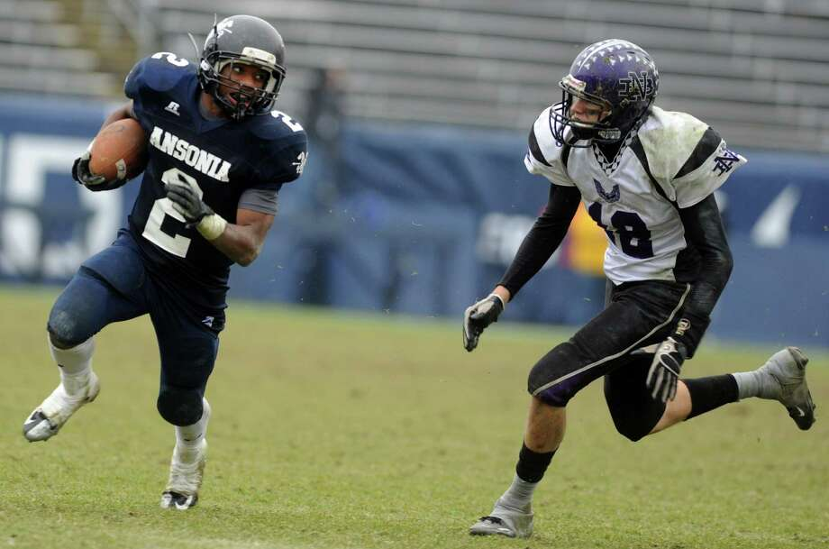 Ansonia's Arkeel Newsome carries the ball as North Branford's Alex McGuigan defends during the Class S state football championship game Saturday, Dec. 8, 2012 at Rentschler Field in East Hartford, Conn. Photo: Autumn Driscoll / Connecticut Post