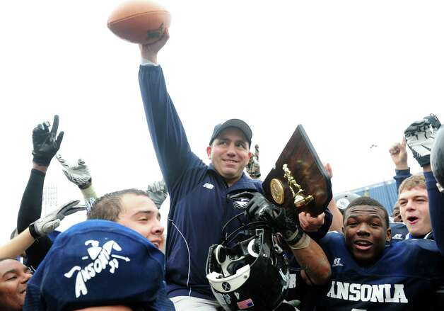 Players lift up Ansonia coach Thomas Brockett as they celebrate their 59 to 26 win over North Branford High School during the Class S state football championship game Saturday, Dec. 8, 2012 at Rentschler Field in East Hartford, Conn. Photo: Autumn Driscoll / Connecticut Post