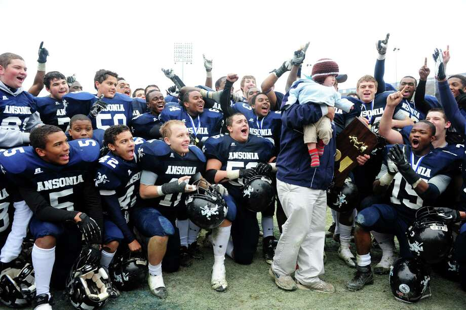 Players cheer as Ansonia coach Thomas Brockett holds his 9-month-son Michael as they celebrate their 59 to 26 win over North Branford High School during the Class S state football championship game Saturday, Dec. 8, 2012 at Rentschler Field in East Hartford, Conn. Photo: Autumn Driscoll / Connecticut Post
