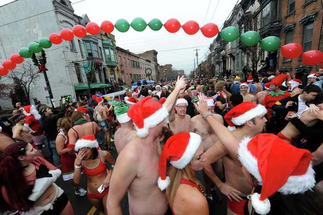 Participants cross the finish line during the 2012 Santa Speedo run on Lark Street in Albany, NY Saturday Dec. 8, 2012. (Michael P. Farrell/Times Union) Photo: Michael P. Farrell