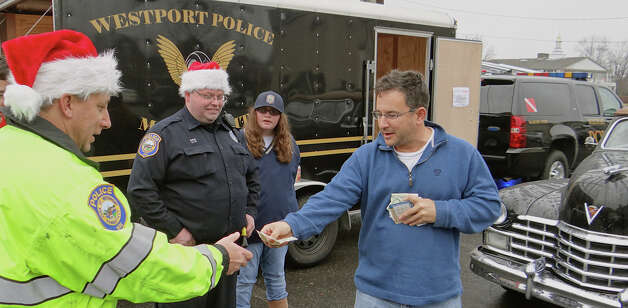 Westport resident Anthony Lofrisco Jr. gives a cash donation to Police Officer Dave Librandi at the site of police officers' annual toy drive as Officer Sean Kelley and Kelley's daughter Renee look on Saturday.  Westport CT 12/8/12 Photo: Mike Lauterborn / Westport News contributed